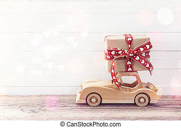 Wooden toy car with a gift box on the roof. White wooden background. Place for text.