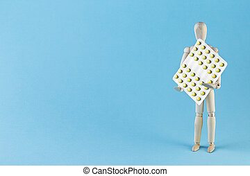 Wooden toy figure with pills on blue background.