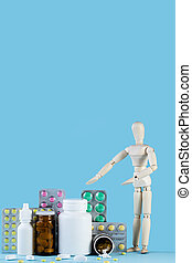 Wooden toy figure with pills on blue background