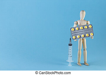 Wooden toy figure with pills on blue trendy background.