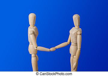 Wooden toy figures handshake on blue