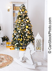 Wooden toy horse, giftboxes, golden christmas decorations balls hanging on a decorative christmas tree.