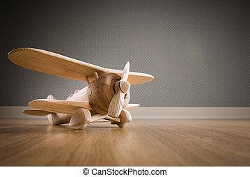 Wooden toy plane hand carved model on hardwood floor.