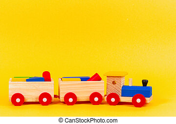 Wooden toy train with colorful blocks on yellow background