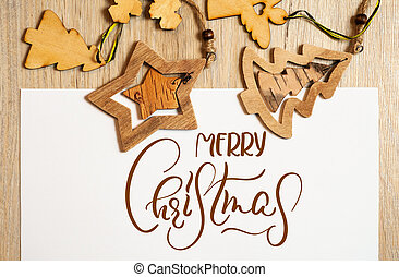 Wooden toys on a white background with text Merry Christmas. Calligraphy lettering