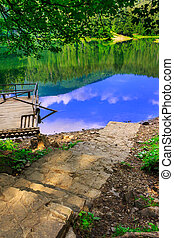wooden transport - stone steps going down to the lake in the...