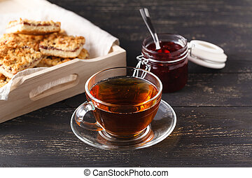 Wooden tray with a cup of tea and cookies