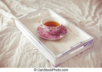 Wooden tray with cup of tea on bed, vintage toned
