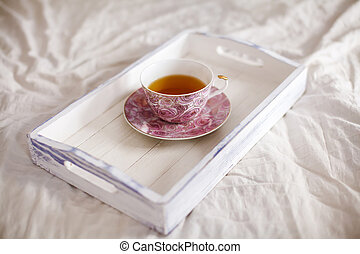 Wooden tray with cup of tea on the bed
