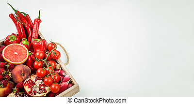 wooden tray with fresh red vegetables and fruits on white background. Healthy eating vegetarian concept.