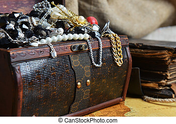 Wooden treasure chest with valuables. beads, necklaces and...