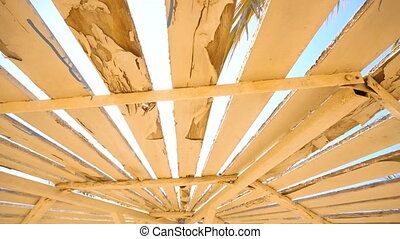 Wooden umbrella in summer with rays of sun
