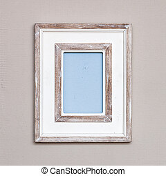 Wooden vintage picture frame on a wall.