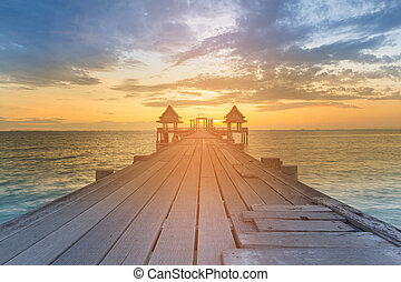 Wooden walking path leading to sunset seacoast