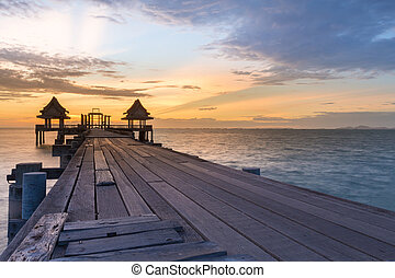 Wooden walking way leading to ocean with sunset skyline