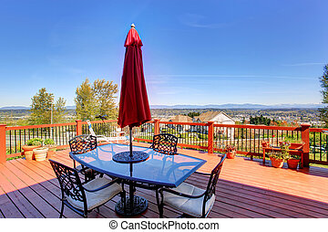 Wooden walkout deck with patio table overlooking beautiful landscape