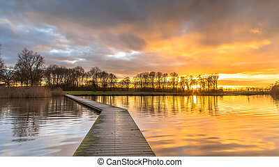 Wooden walkway in lake under orange sunset in december. Drenthe, The Netherlands