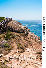 Wooden walkway to beautiful Carvoeiro beach with cliff and rock formation Algarve region Portugal