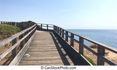 Wooden walkway to beautiful Carvoeiro beach with cliff and...