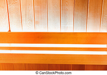 Wooden wall of traditional Finnish sauna with bright lighting. Background for design
