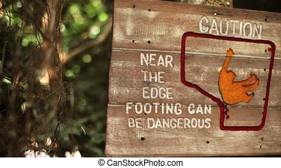 Wooden warning sign edge footing can be dangerous - Caution...