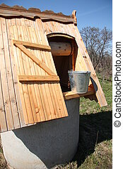 Wooden well with a bucket of water