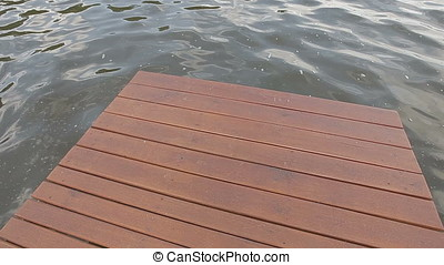 Wooden Wharf Foamy Waters Canted Shot - Wooden wharf against...