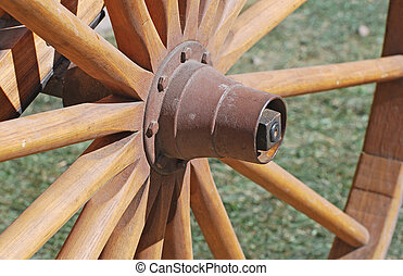Wooden wheel on handcart with rusty hub.