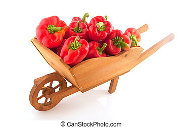 Wooden wheelbarrow full with red paprika