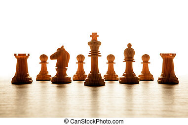 wooden white chess pieces lined up in a row