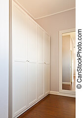 Wooden white wardrobe in white room for store cloths