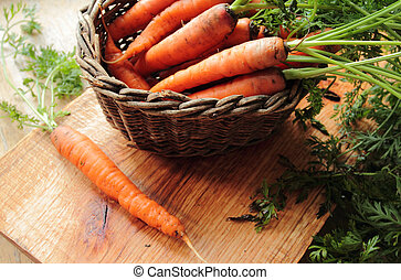 Wooden wicker with fresh carrots on a kitchen table