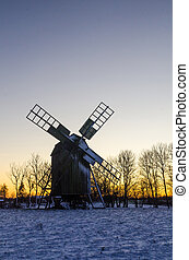 Wooden windmill by sunset in winter time