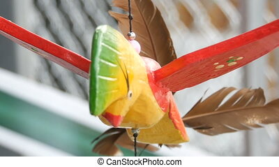 Wooden windmill kinetic sculpture of colorful bird develops...