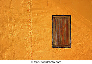 Wooden window on yellow wall.