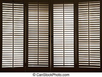 Wooden Window Shutters - Wooden shutters in front of bright...