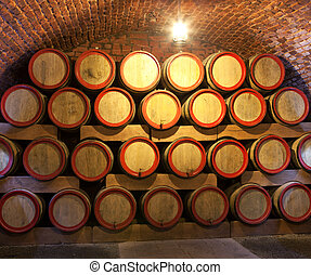Wooden wine barrels are stored in winery cellar