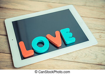 Wooden word LOVE on tablet in vintage style