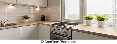 Wooden worktops and white cupboards in cozy kitchen