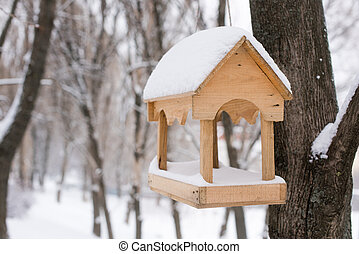 Wooden yellow birds feeder at winter forest