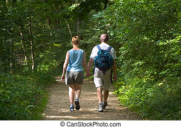 Couple holding hands on woodland walk in dappled sunlight.