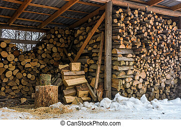 woodshed full of chopped firewood in winter - woodshed full...