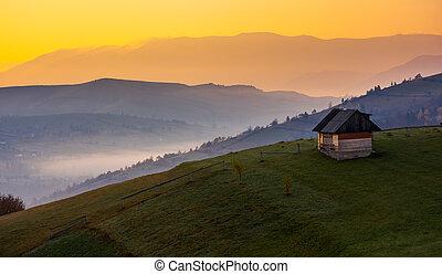 woodshed on a hillside at sunrise