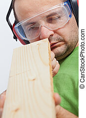Woodwork - man checking linearity of wooden planck - closeup