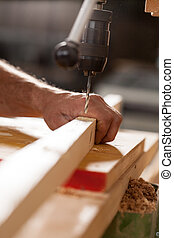woodworker drilling a plank with machinery