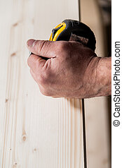 woodworker hand holding a measuring tape