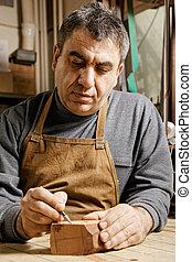 Woodworker in workshop drawing pipe on wood billet
