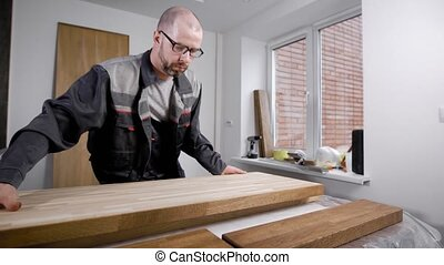 woodworker is putting timber board on a table in a workshop of small carpentry, preparing for processing