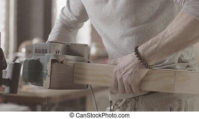 Woodworker treats edge of wooden board by belt sander. Manufacturer