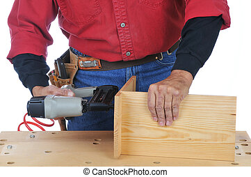 Woodworker using a Nail Gun - isolated over white
